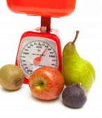 Ripe Fruit And Kitchen Scales Close Up On A White Background