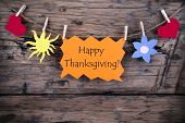 stock photo of happy thanksgiving  - The Words Happy Thanksgiving on a Orange Banner Hanging on a Line with Heart and Sun Symbols Wooden Background - JPG