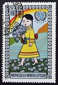 MONGOLIA - CIRCA 1977: stamp printed in Mongolia shows Girl cwith bouquet of flowers circa 1977