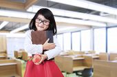 picture of indian apple  - Cheerful little girl standing in class while holding a book and apple - JPG