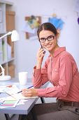 Young attractive female fashion designer working at office desk, drawing while talking on mobile