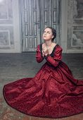stock photo of pompous  - Young beautiful medieval woman in long red dress praying in the old room - JPG