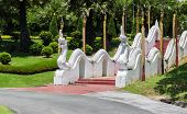image of garden sculpture  - the white naga sculpture on staircase rail in the garden - JPG