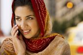 stock photo of dupatta  - Middle Eastern woman talking on cell phone - JPG