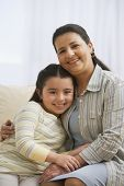 Hispanic mother hugging daughter
