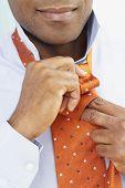 African American man tying necktie