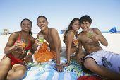 Hispanic couples holding drinks at beach