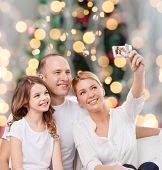 family, holidays, technology and people - smiling mother, father and little girl making selfie with camera over christmas tree lights background