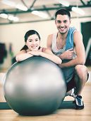 fitness, sport, training, gym and lifestyle concept - two smiling people with fitness ball in the gy