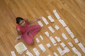 Hispanic woman surrounded by receipts