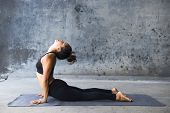 foto of cobra  - Young woman practicing yoga in a urban background - JPG