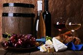Supper consisting of Camembert and Brie cheese, honey wine and grapes on napkin in basket and wine barrel on wooden table on brown background
