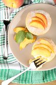 Tasty mini cakes with fresh peach, on plate