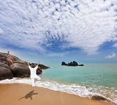 Thailand. Gorgeous beach on the Andaman Sea. Middle-aged woman dressed in white doing yoga.  Pose