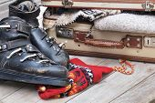 stock photo of ski boots  - small open suitcase full of warm clothes with old ski boots - JPG