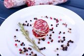 French salami and pepper on plate on dark blue wooden background