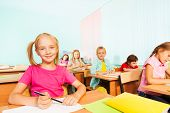 Children write in exercise books and sit at tables