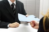 Employment Interview With Female Applicant Handing Over A File Containing Her Curriculum Vitae To Th