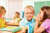 Girl telling secret to smiling boy in classroom