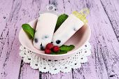 Tasty ice cream pops with fresh berries on plate, on color wooden background