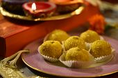 picture of pooja  - A plate full of Indian sweet and illuminated oil lamps at the background  - JPG