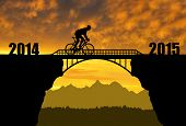 stock photo of exercise bike  - Cyclist riding across the bridge at sunset  - JPG
