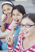 Hispanic teenaged girls eating candy