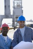 African American male construction workers with blueprints
