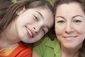 Hispanic girl leaning on mother's shoulder