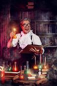Portrait of a crazy medieval scientist working in his laboratory. Alchemist. Halloween.
