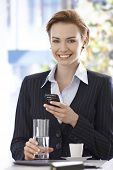 Portrait of happy young businesswoman using mobilephone, drinking water and coffee.