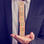 Businessman Holding A Stack Of Checked Boxes