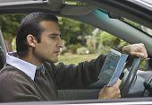 Hispanic man looking at map in car