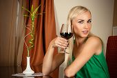beautiful girl sitting with a glass of wine