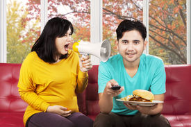 foto of annoying  - Hispanic pregnant woman feeling annoyed to her husband and yelling with a megaphone - JPG