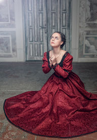 picture of pompous  - Young beautiful medieval woman in long red dress praying in the old room - JPG