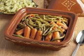 Moroccan square tagine with meat, green beans and carrots on the table