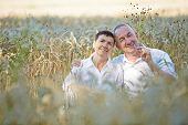 Happy senior couple sitting in a wheat field in summer