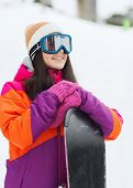 winter, leisure, sport and people concept - happy young woman in ski goggles with snowboard outdoors