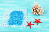 Sea salt crystals with sea shells, star fish  on color wooden background
