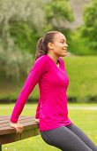 fitness, sport, training, park and lifestyle concept - smiling african american woman doing push-ups on bench outdoors
