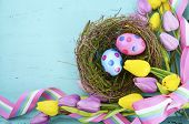 Happy Easter Background With Polka Dot Easter Eggs In Birds Nest, And Yellow And Purple Silk Tulips