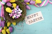 stock photo of bird-nest  - Happy Easter background with painted Easter eggs in birds nest and yellow and purple silk tulips and ribbon on vintage style rustic distressed aqua blue wood table with greeting tag - JPG
