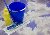 Bucket And Mop Over A Blue Cloudy Sky