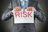 stock photo of tears  - Businessman Tearing The Word Risk On Paper Over Gray Background - JPG