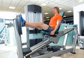 Gym seated leg press machine blond man workout at indoor