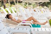 Woman In Swimwear Sunbathing On Lounge Chair