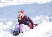 stock photo of sled  - little girl plays with sledding on snow in the winter in the mountains - JPG