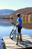 pic of riding-crop  - Young athlete standing on a rock with bicycle - JPG