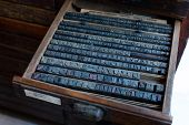 stock photo of armoire  - Old vintage metal printing press letters in a drawer - JPG